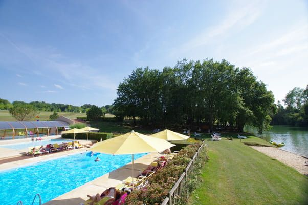 Piscine en bord d'étang sous le ciel bleu de Dordogne
